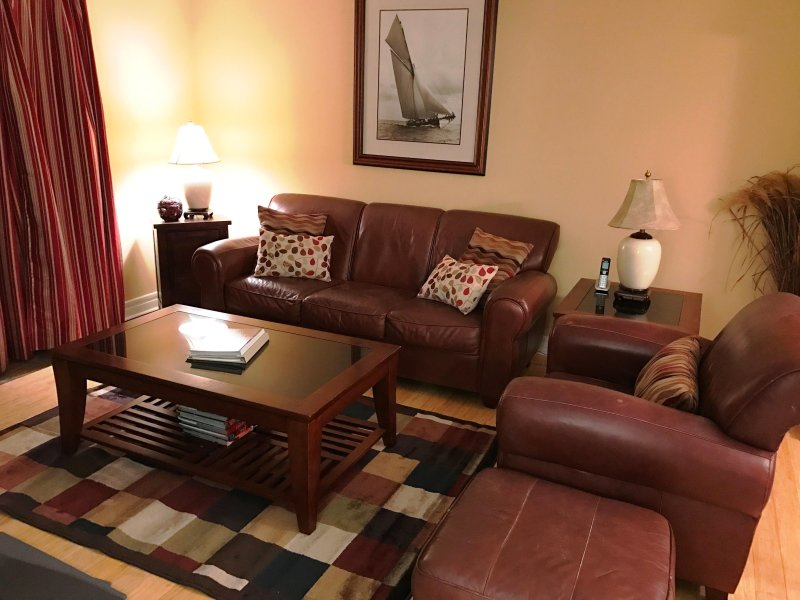 Family room is well decorated and very comfortable. Leather couches and chairs with a TV.