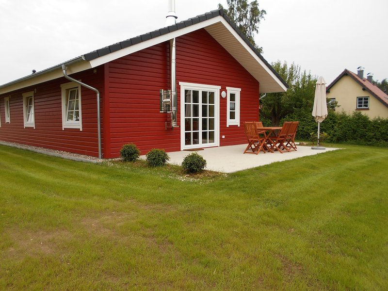Die Rückseite des Ferienhauses mit der Terrasse. Von dort der  Blick in den Garten und über das Land