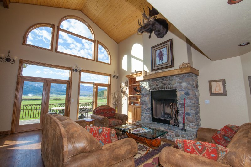 Great room featuring floor to ceiling windows and a wood burning fireplace.