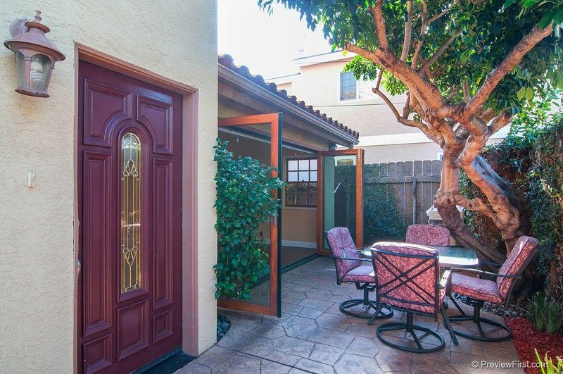 Private fenced long patio with seating for 13. See next photo.