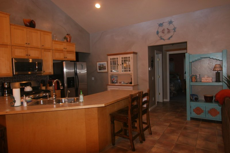 Open kitchen loaded with dishes , small appliances and stainless steel appliances