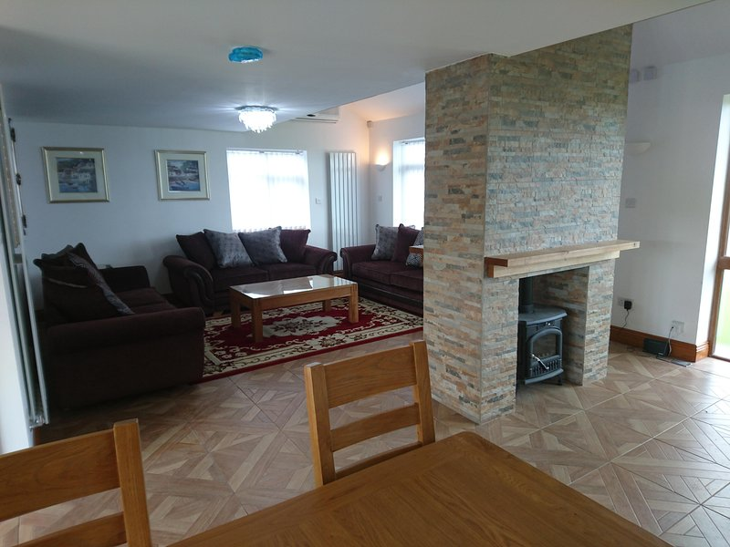 View from the dining area showing the lounge and see-through log burner