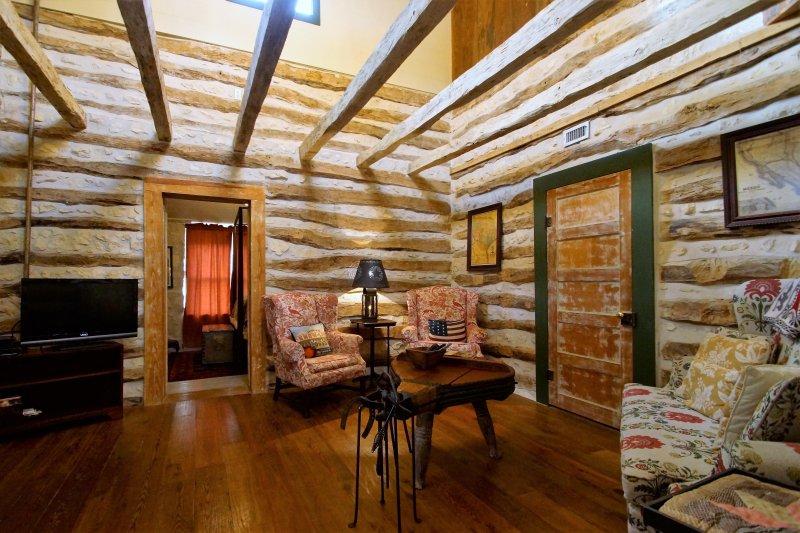 Woonkamer met houten vloer en open originele eiken balken.