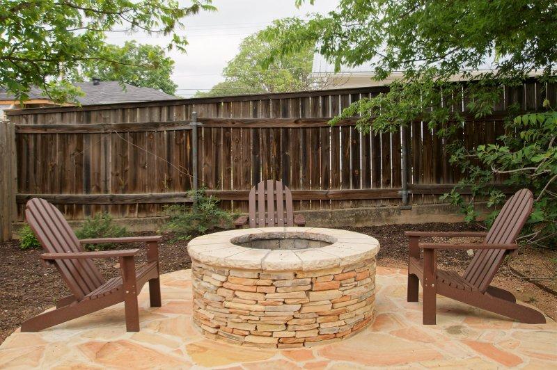 Vuurkorf strekt zich uit van de pergola en is onderdeel van de buitentuin.