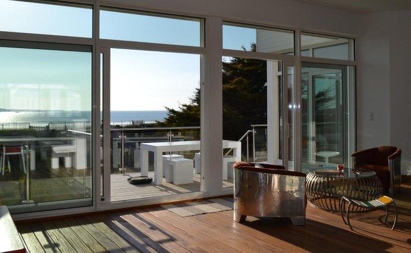 Salon et terrasse au soleil en face de la plage