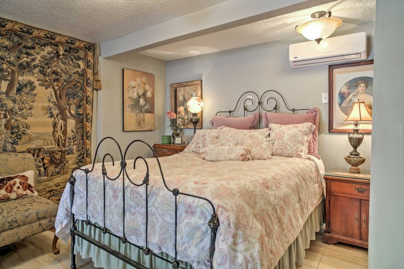 The bedroom area features a full-sized bed, a lovely iron bed frame, and wooden chests for convenient storage.