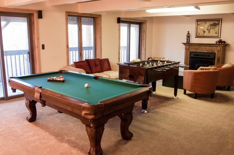 Basement with pool table, foostable, 4 club chairs and a cozy love seat