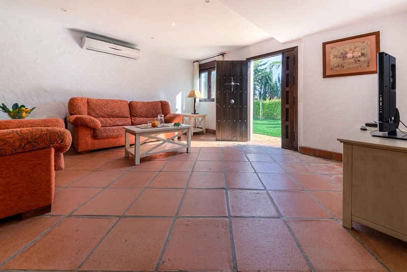Sofás, mesa y tv del salón del apartamento Hierbabuena en Hacienda Roche Viejo en Conil
