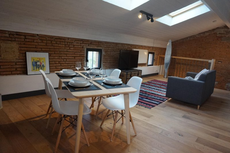 Large living room-kitchen with oak floors and Toulouse brick walls.