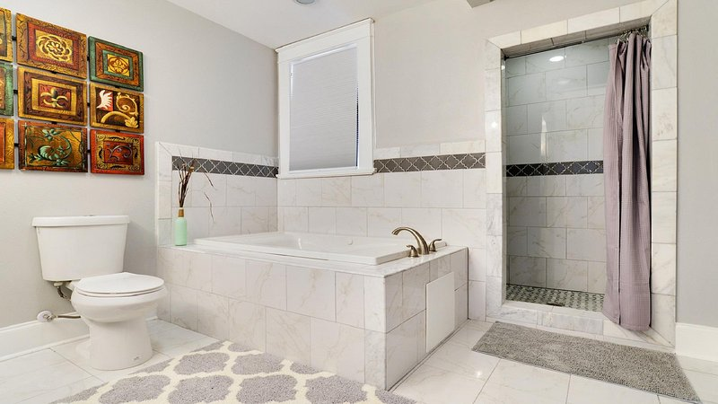 Master bath with marble tiles and Jacuzzi tub and rainfall shower.