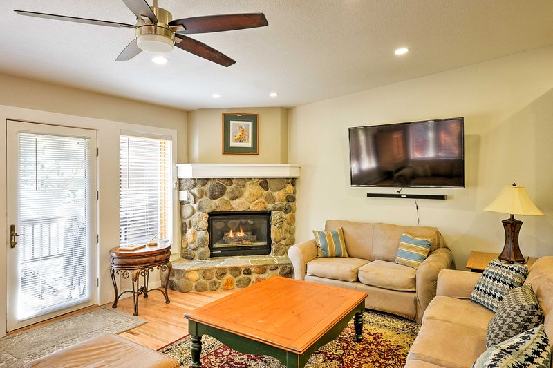 The living room features a stone fireplace and flat-screen cable TV.