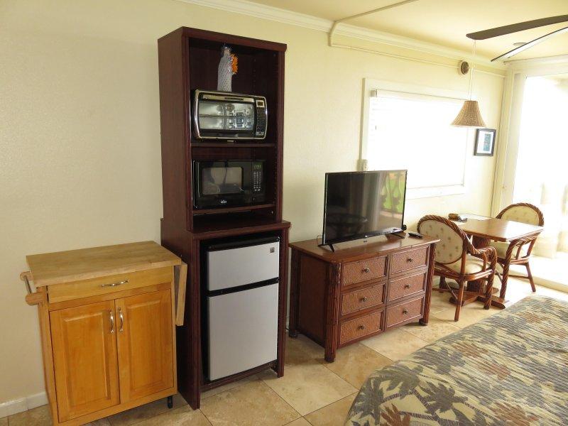 Uitzicht op kar, apparaten, tv, laden, en zithoek.