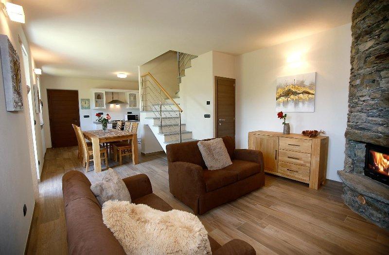 Gran espacio abierto con cocina, mesa de comedor, sala de estar y chimenea.