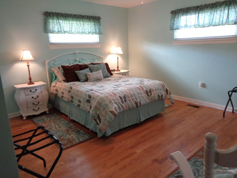 master bedroom w/ queen size bed and private bath w/ corner shower