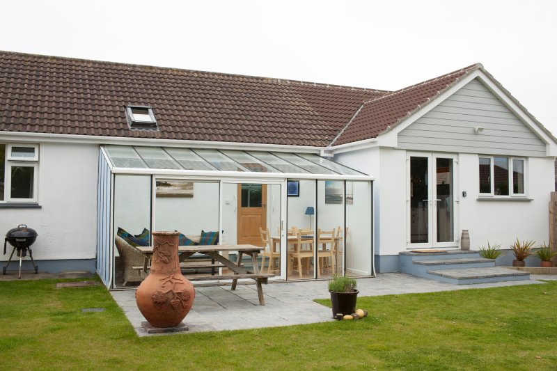 Large conservatory and patio space lovely for socialising with access to kitchen.