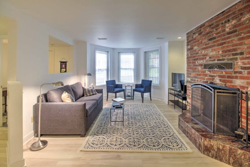 Step inside to find an original brick fireplace contrasting the apartment's sleek, modern decor.