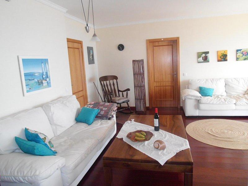 A sala de estar inclui dois sofás confortáveis, uma cadeira de balanço e uma mesa de madeira maciça.