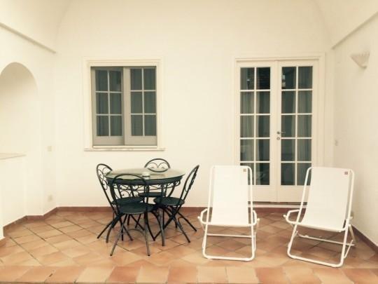 Terraza privada equipada con mesa, sillas y tumbonas.
