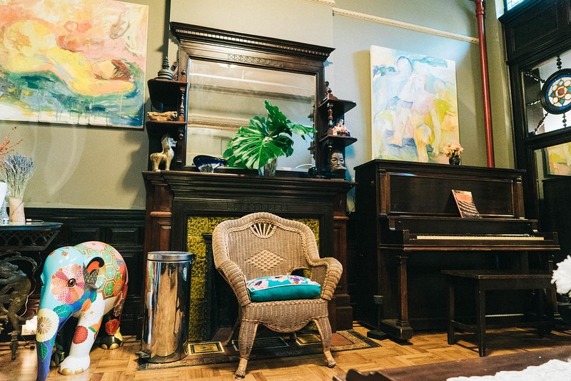 Entertaining corner with the vintage piano and fireplace.
