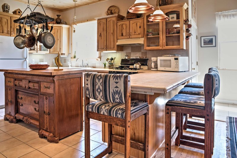 Equipped with rustic wood cabinetry, ample counter space and all your essential appliances, this kitchen makes meal prep easy as pie.