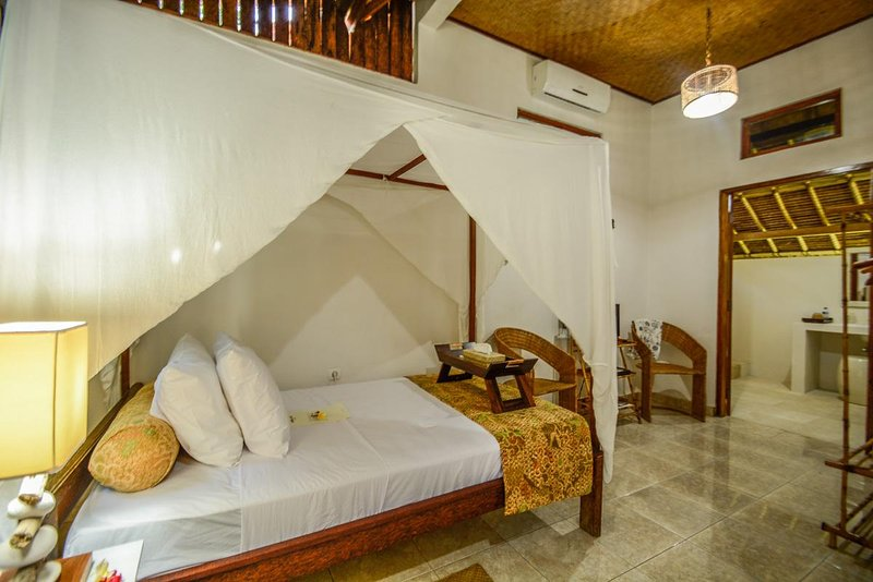 Large single bedroom with air conditioning and fan. Artifacts and antiques decorate and batik fabric