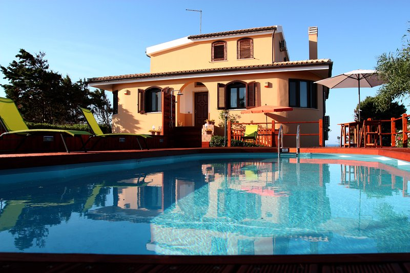 la fachada de la casa con piscina en primer plano