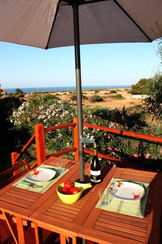 mesa en la terraza de la piscina con vistas al mar