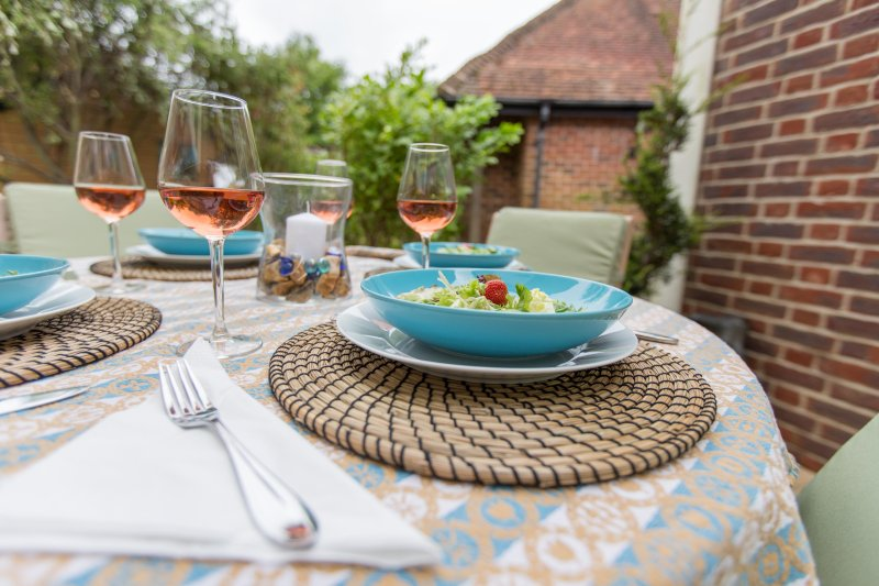 Alfresco dining on banks of millstream with sea views in the distance