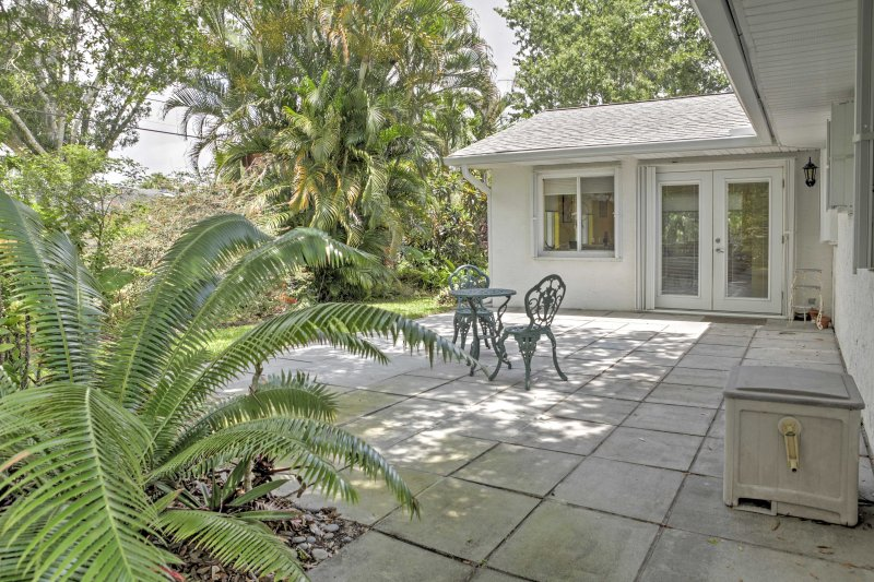 The home is located on a large lot surrounded by shady palm trees.