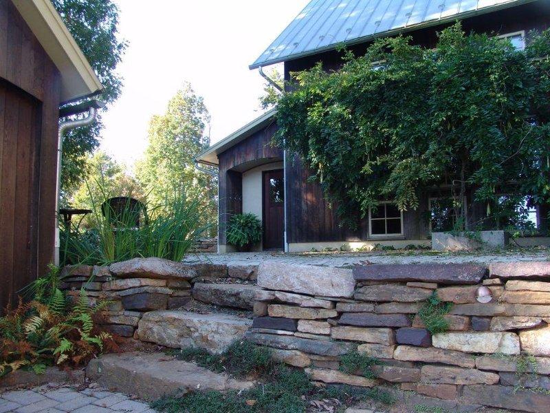Acercarse a la casa por un camino a lo largo de una pared de piedra con la iluminación de acento en la noche y agua característica