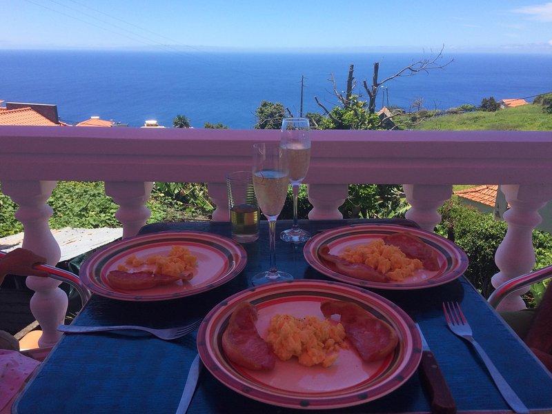 El desayuno en la terraza y disfrutar de una vista al mar bajo la sombra del toldo de color de rosa