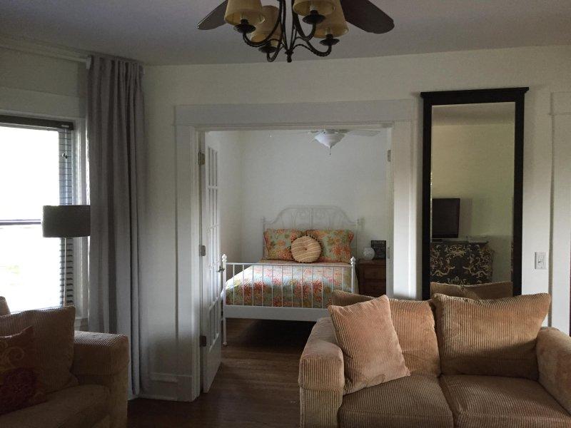 Vy över sovrum med franska dörrar. Full säng.