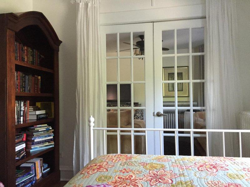 inifrån ser till vardagsrummet genom franska dörrar. Dra för gardinerna för privatlivet.
