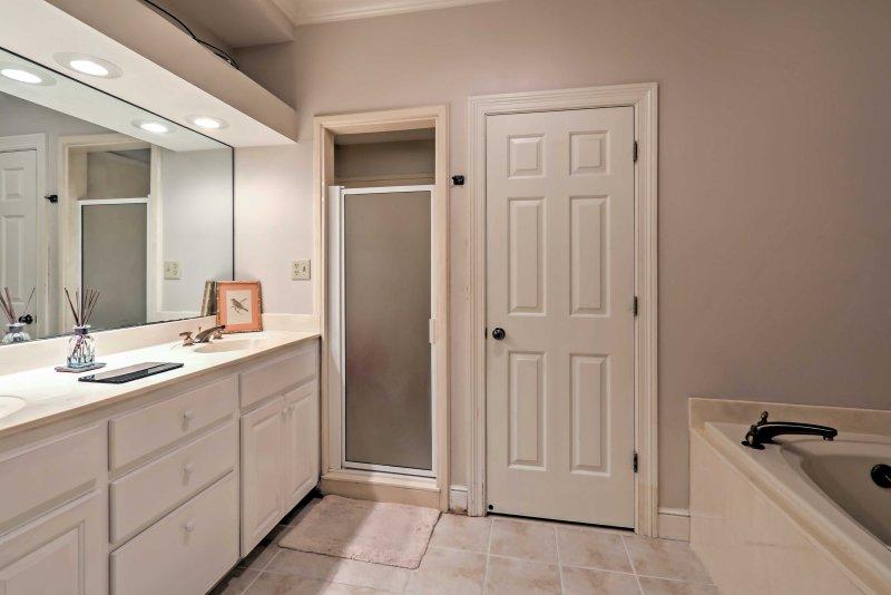 Cette salle de bains immaculée dispose d'une cabine de douche et d'une baignoire à remous.