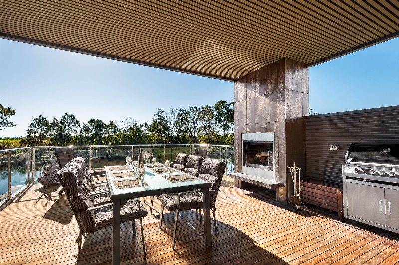 The sunny, north-facing deck with open fireplace, BBQ, dining setting and sun lounges