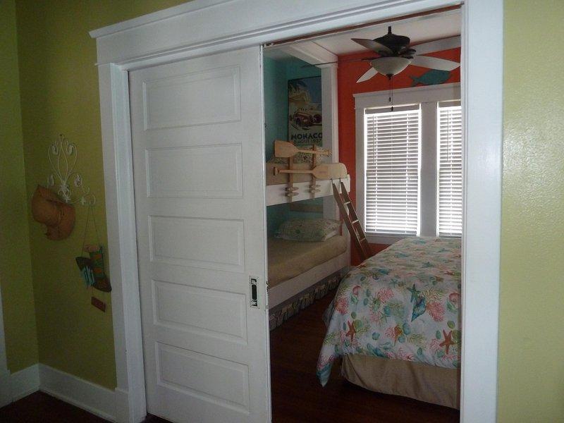 Chambre 1 a un lit king-size et deux lits superposés jumeaux avec des portes coulissantes pour la vie privée