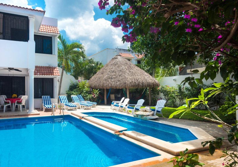 View across the 2-level pool toward the garden and palapa roofed patio.