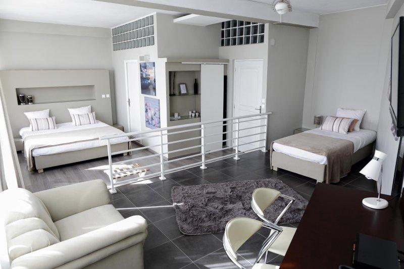 sala de família com uma cama queen size e cama de solteiro