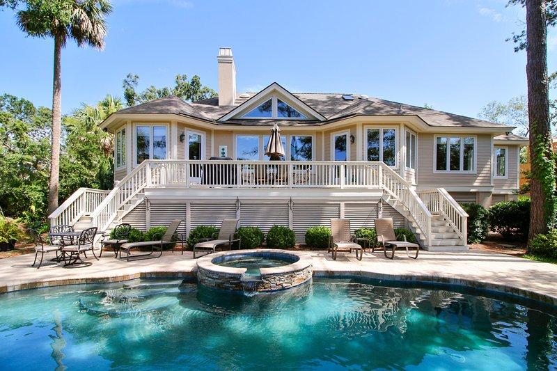 Parte traseira da casa. áreas de estar à beira da piscina e deck traseiro.