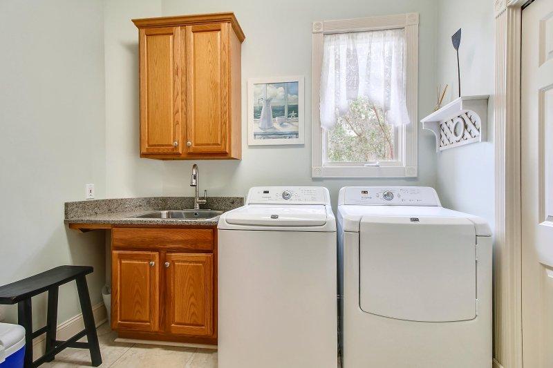 Salle de lavage avec laveuse, sécheuse et évier.
