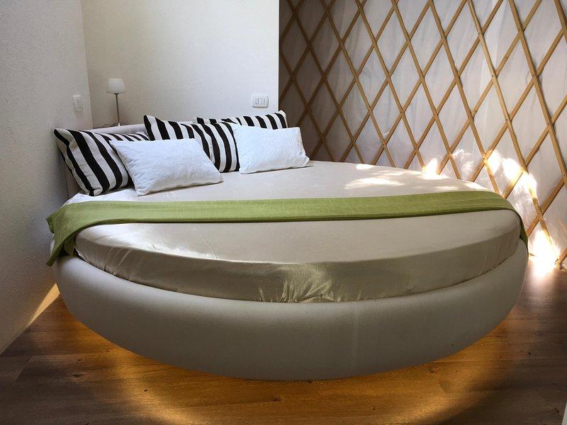Très grand lit rond sous un dôme central dans une chambre