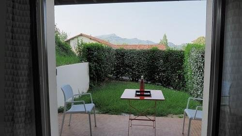 The private terrace with table and chairs and view of the mountains