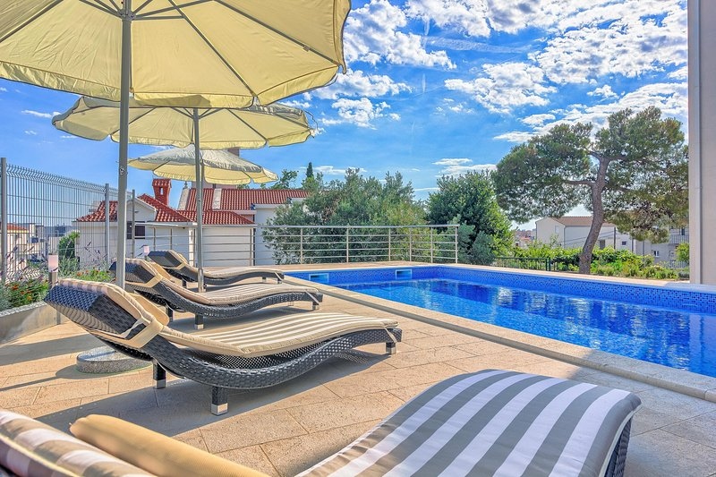 Pool area with loungers and parasols