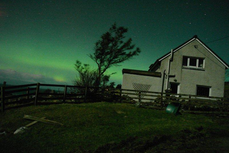 Eerily beautiful, dancing green curtain of the Northern Lights (Aurora Borealis) over Tir Nan Og