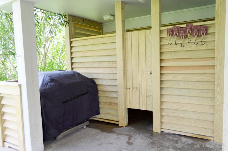 Outdoor charcoal grill and updated outdoor shower and changing area.