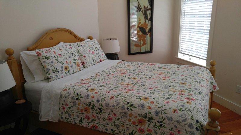 Dormitorio con cama de matrimonio y techos altos