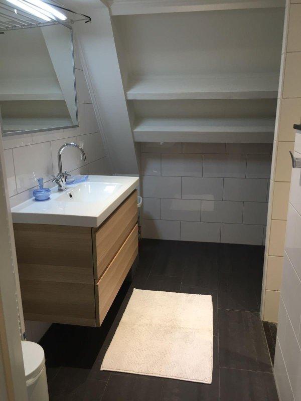 salle de bains avec douche, machine à laver et sèche-linge