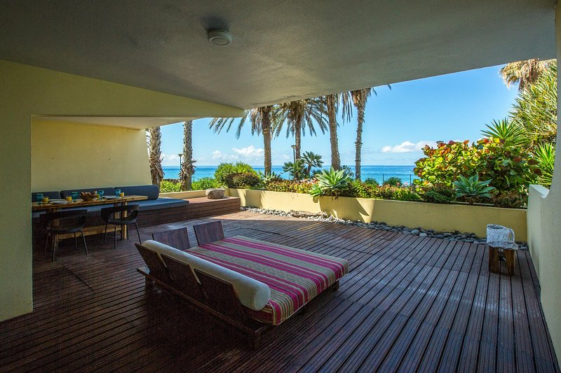 Terrific deck, palm trees and the ocean just steps away.