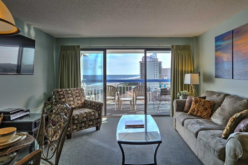 Seafoam pareti verdi e originali opere d'arte spiaggia a tema vi saluta come si cammina in questo condominio con vista spettacolare sul bellissimo mare blu e spiagge di sabbia bianca.