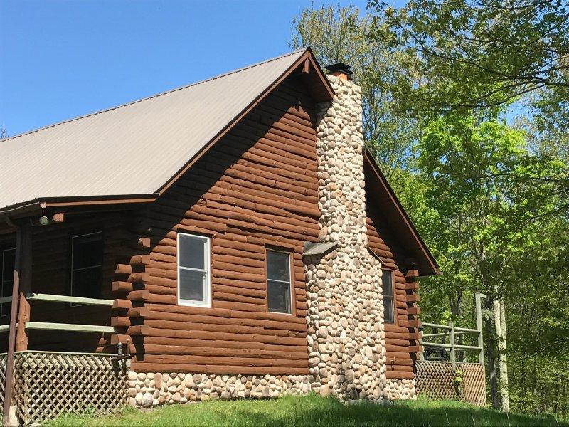 Mano de la casa cabaña de troncos curados